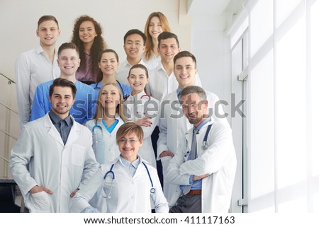 A group of doctors and nurses standing on the stairs in the hospital, indoors - stock photo