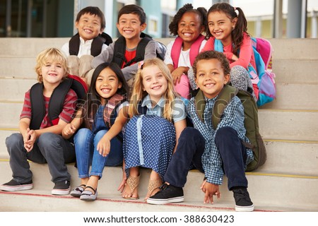 A group of elementary school kids sitting on school steps - stock photo