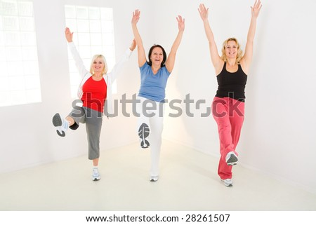 A group of exercising women. They're smiling and looking at camera. - stock photo