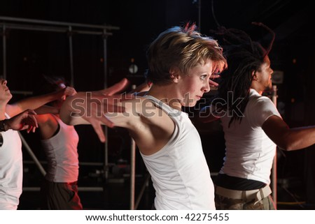 A group of female and male freestyle hip-hop dancers during dance training session on stage. Lit with spotlights. Movement on edges of dancers - stock photo