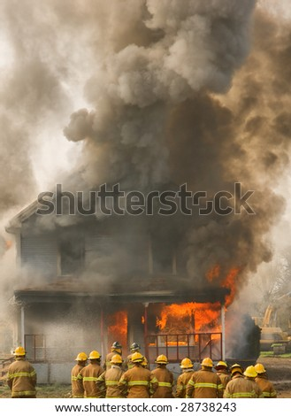 A group of firemen stand in front of a flame engulfed house - stock photo