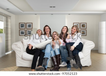 A group of five happy women of different ages laughing in the living room - stock photo