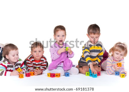 A group of five kids with different emotions are lying or sitting and playing colorful blocks; isolated on the white background - stock photo