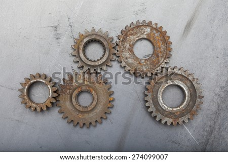 A group of five rusty metal gears are linked together on a grungy steel background. - stock photo