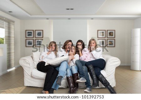 A group of five women of different ages sitting on the livingroom looking at the camera with scared expressions - stock photo