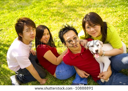 a group of four asian teens laying back on grass holding a white puppy labrador - stock photo