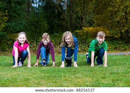 A group of four children lined up ready to race in a park. - stock photo