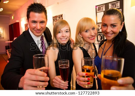 A group of four friends celebrating in a bar and posing for the camera - stock photo