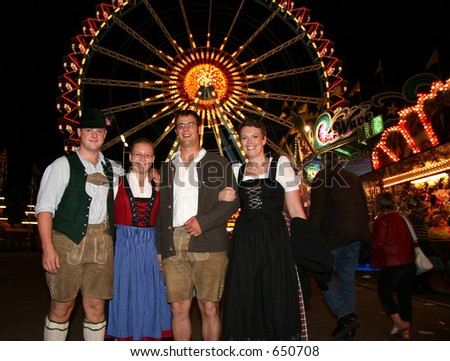 A group of four German Oktoberfest fans in Traditional costume - stock photo