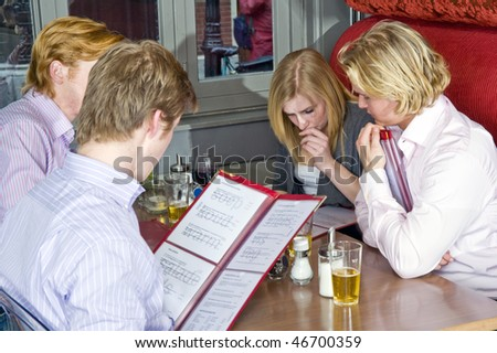 a group of four people choosing dishes from the menu in a restaurant - stock photo