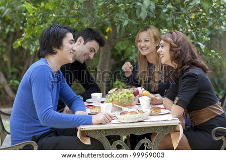 A group of four young friends enjoy a healthy snack and coffie at an outdoor restaurant - stock photo