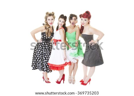 A group of four young girls dressed in Rockabilly, pinup dresses. Shot on white background. - stock photo