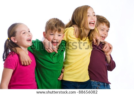 A group of four young kids wearing colorful shirts and having fun. - stock photo