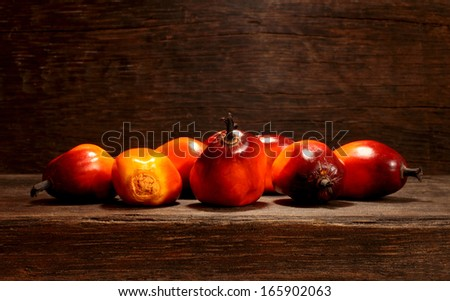 A group of fresh and ripe oil palm fruits on table - stock photo