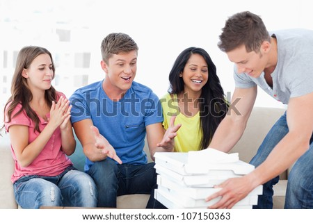 A group of friends celebrate as a man brings them some pizza - stock photo