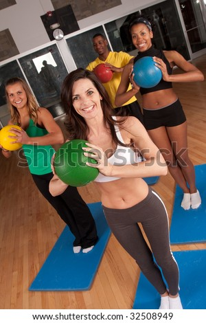 a group of friends in a fitness class using mats and medicine balls - stock photo