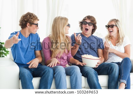 A group of friends laugh and joke around as they wear 3D glasses - stock photo