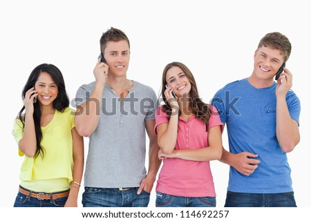 A group of friends of smiling as they all make calls and look into the camera - stock photo