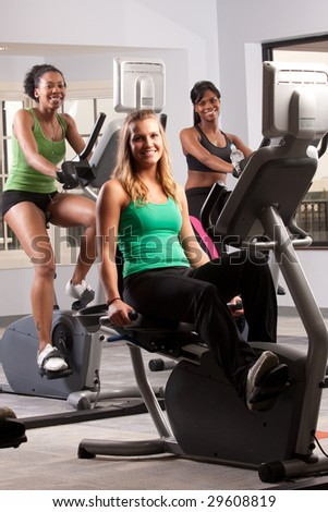 a group of friends on cardio equipment in the gym - stock photo