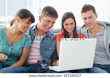 A group of friends sitting on the couch together smiling as they look at a laptop - stock photo
