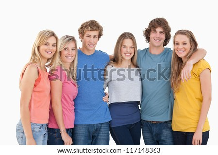 A group of friends smiling and holding each other while looking at the camera - stock photo