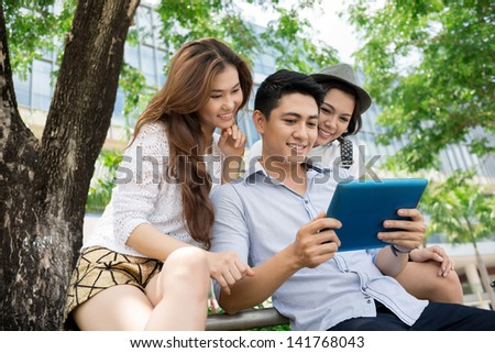 A group of friends with a tablet outside - stock photo