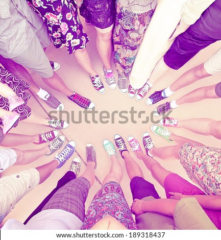 a group of friends with their legs in a complete circle done with a retro vintage instagram filter  - stock photo