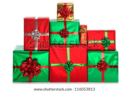 A group of gift wrapped presents in bright shiny wrapping paper with bows and ribbons, isolated on a white background. - stock photo