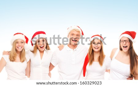 A group of happy and emotional teenagers in Christmas hats over blue background - stock photo