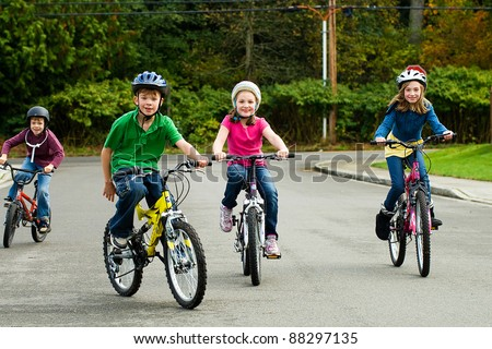 A group of happy children safely riding their bicycle on the street while wearing a helmet. - stock photo