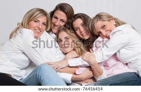 A group of 5 happy women of different ages cuddling - stock photo