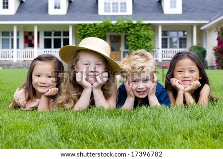 A group of kids laying in the grass. Diveristy and friendship - stock photo
