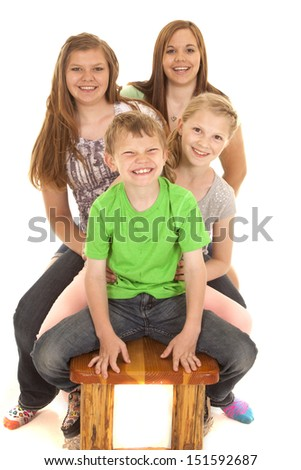 A group of kids sitting on a bench with smiles on their faces. - stock photo