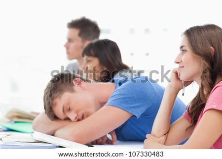 A group of listening students in class as another student has fallen asleep - stock photo