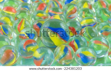 A group of marbles with a large shooter marble on top. - stock photo