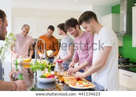 A group of men are preparing a meal together in the kitchen. - stock photo