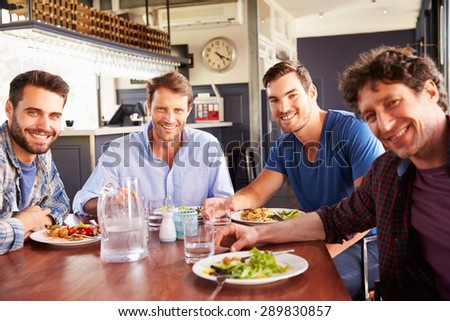 A group of men having lunch in a restaurant - stock photo