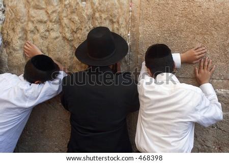 A group of men praying at the wailing wall. - stock photo