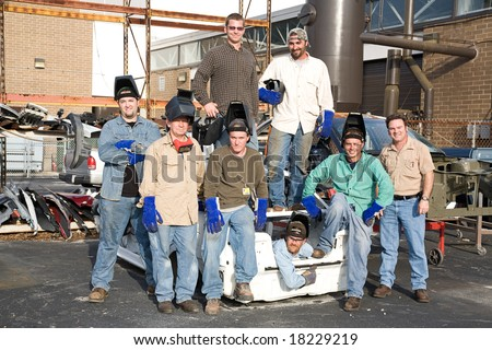A group of metal workers posing with their supervisor in a scrap metal car. - stock photo
