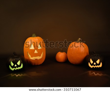 A group of orange scary pumpkins are on an isolated black background with a text area to add your message. - stock photo