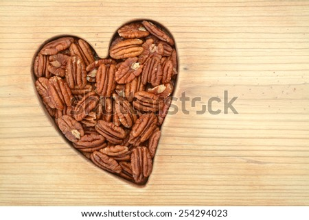 a group of pecan halves on wooden flat in heart shape - stock photo