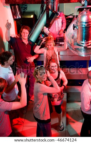 A group of people enjoying themselves at a party in a nightclub. - stock photo