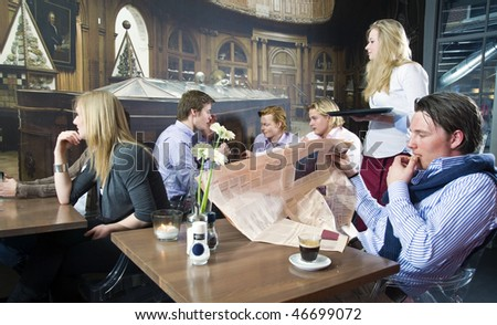 A group of people having a drink in a cafe - stock photo