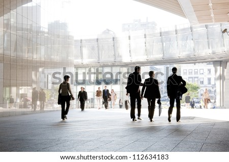 A group of people is against the backdrop of modern buildings. Blurred motion. Silhouette. - stock photo