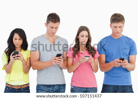 A group of people using their phones and sending texts as they stand beside each other - stock photo