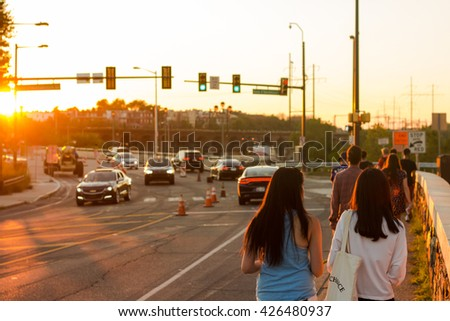 A group of people walk along a sidewalk, with the sun setting in front of them - stock photo