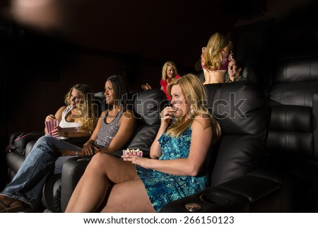 A group of people watching a movie showing emotion as a couple makes out in the back - stock photo