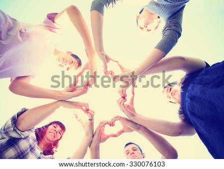 a group of people with their hands in a circle making heart shapes toned with a retro vintage instagram filter app or action effect - stock photo