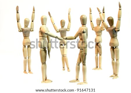 A group of people (wooden doll) cheering when two person shake hand depicting a deal or agreement - stock photo