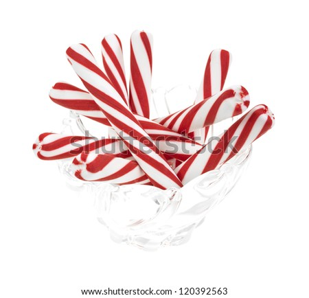A group of peppermint candy sticks in a glass bowl on a white background. - stock photo